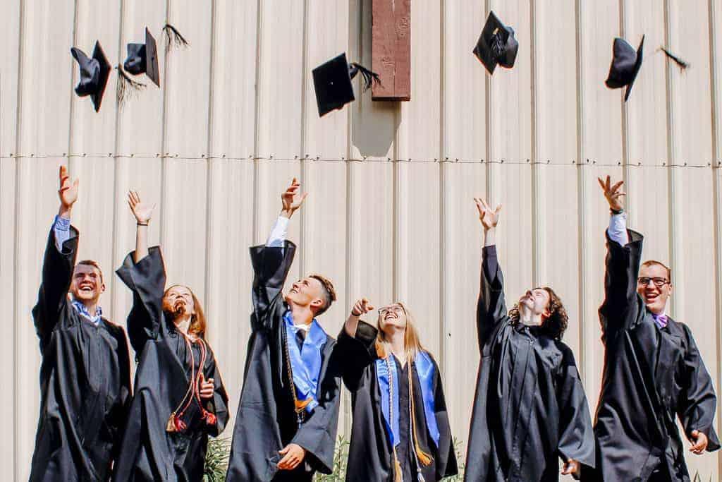 Graduates throwing cap in air