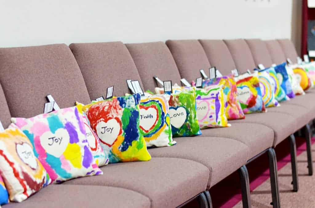 Student painted pillows with texts of joy, faith, love, and believe